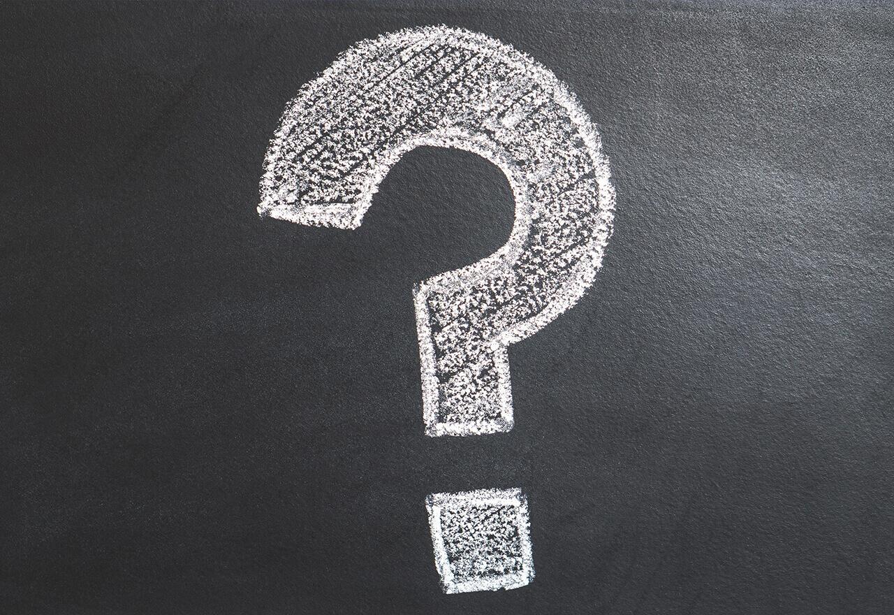 Ein mit Kreide gezeichnetes Fragezeichen auf einer schwarzen Tafel.