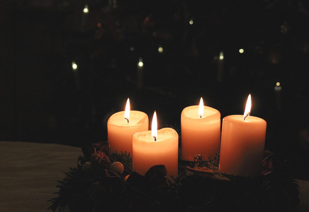Ein Adventkranz mit vier brennenden Kerzen im Dunkeln.