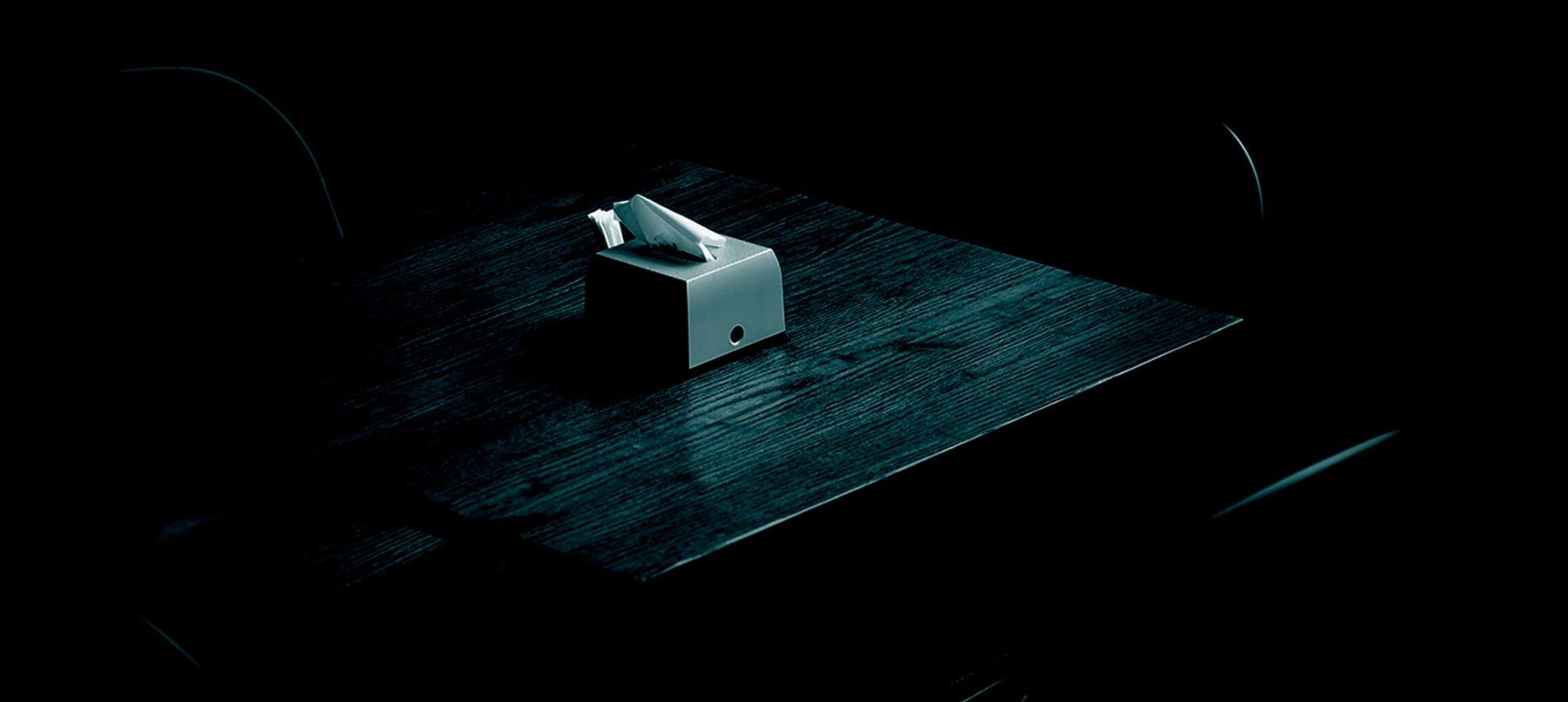 Ein Tisch im Dunkeln, darauf steht eine Box Taschentücher.