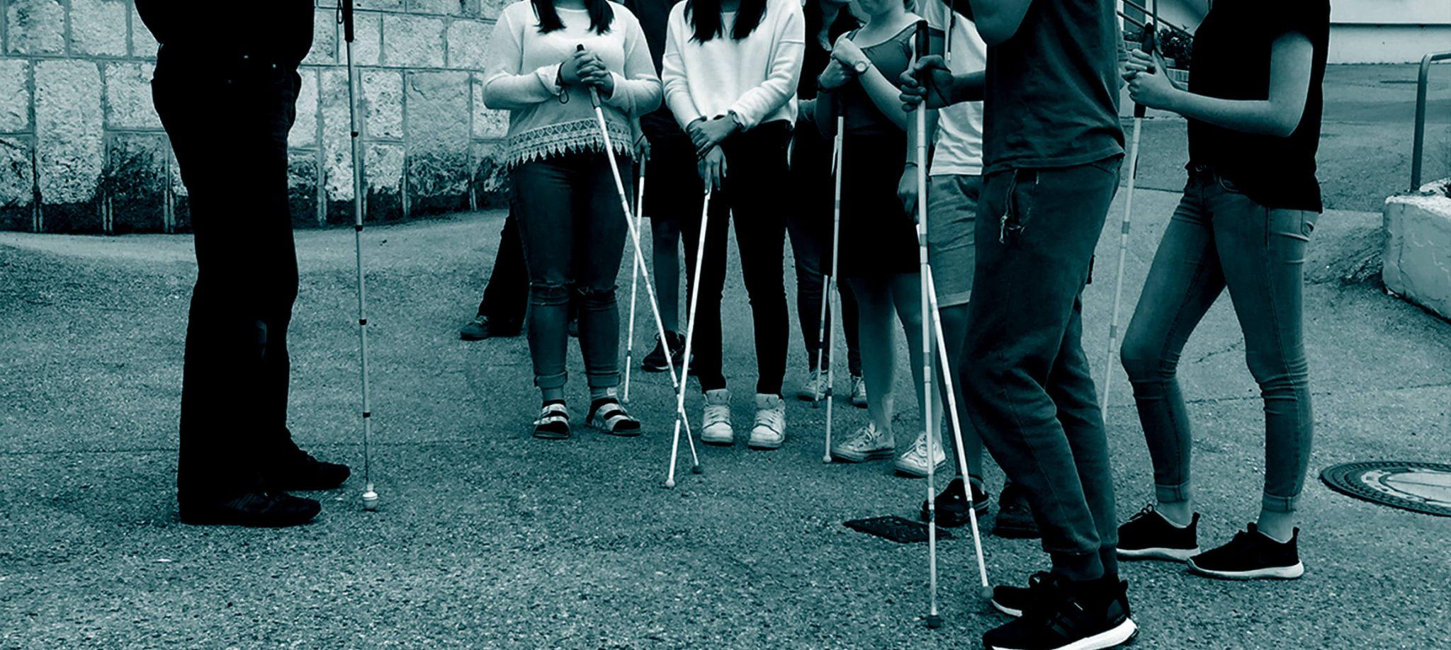 Harald steht vor einer Gruppe SchülerInnen, die SchülerInnen haben Dunkelbrillen auf und einen Blindenstock in der Hand.