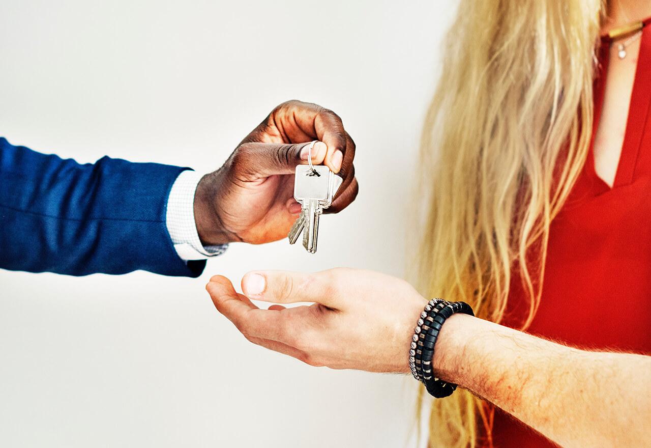 Eine Hand die einer anderen Hand Wohnungsschlüssel überreicht