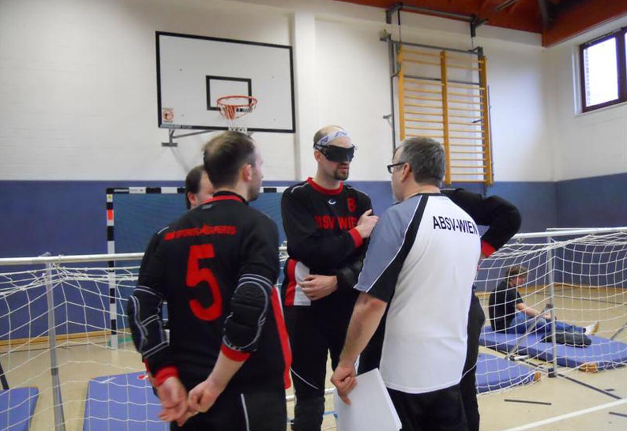 Einige TorballspielerInnen halten zusammen mit dem Trainer eine Teambesprechung