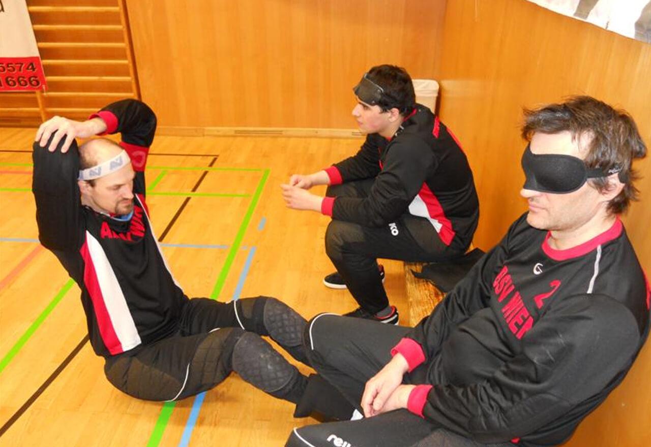 2 Torballspieler sitzen auf der Seitenbank, ein anderer sitzt davor auf dem Boden und macht Dehnübungen.