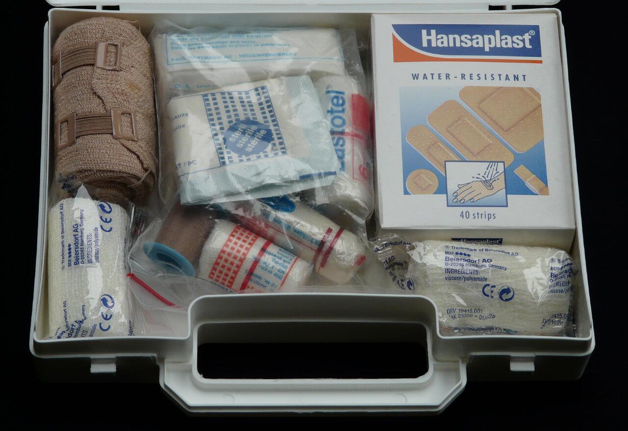 Eine Nahaufnahme eines aufgeklappten Erste-Hilfe-Koffers mit Pflastern, Mullbinden, Verbänden, etc.