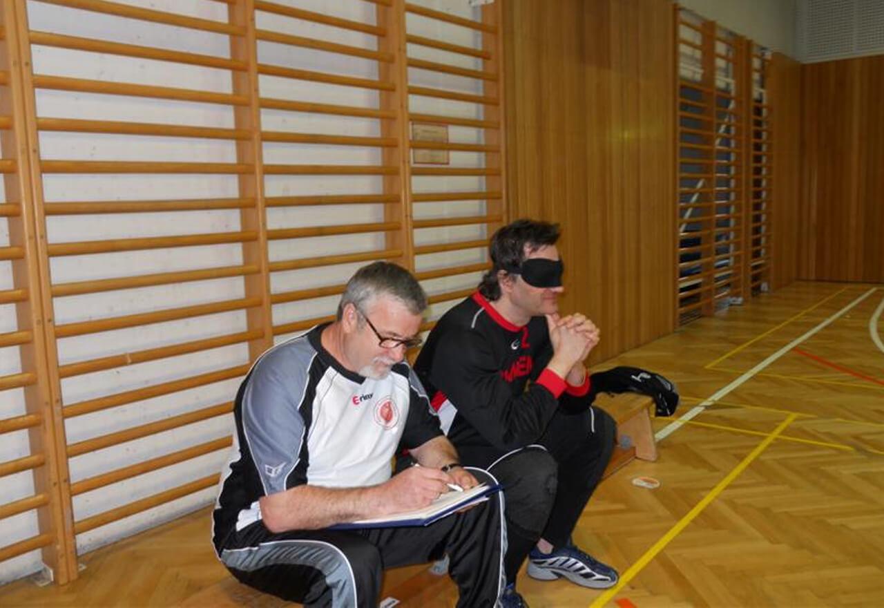 Harald und der Trainer sitzen auf einer Bank an der Seite des Spielfeldes. Der Trainer notiert gerade etwas.