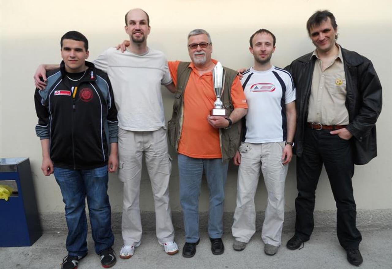 4 Torballspieler stehen umarmt nebeneinander, in der Mitte der Trainer samt Pokal.