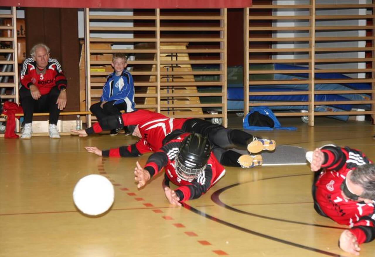 3 TorballspielerInnen versuchen den Ball zu erwischen. Eine Person trägt einen Helm.