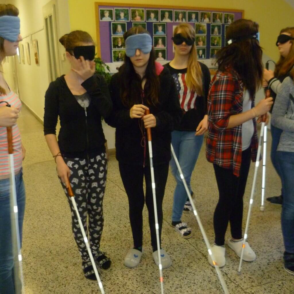 Einige Jugendliche mit Blindenstock und Dunkelbrille stehen im Halbkreis