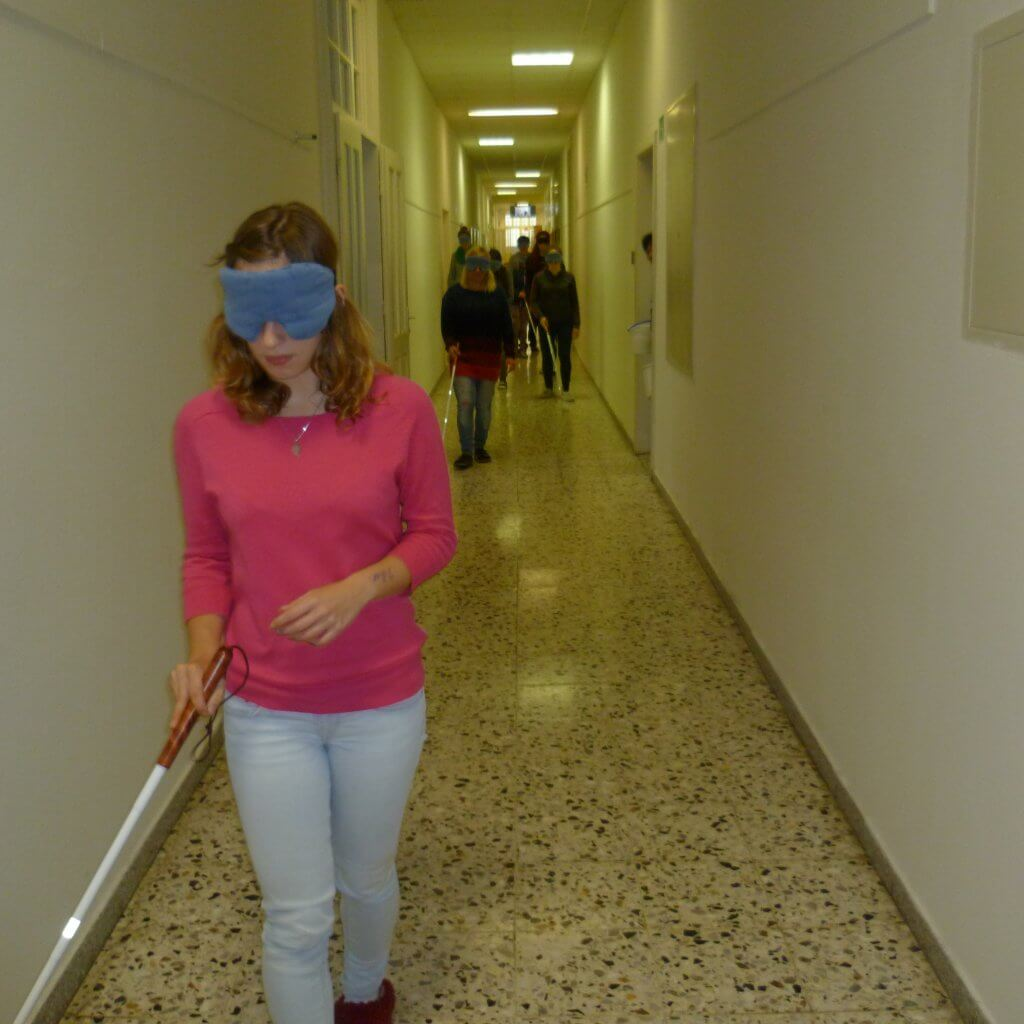 Jugendliche mit Blindenstock und Dunkelbrille geht in Gang auf Kamera zu