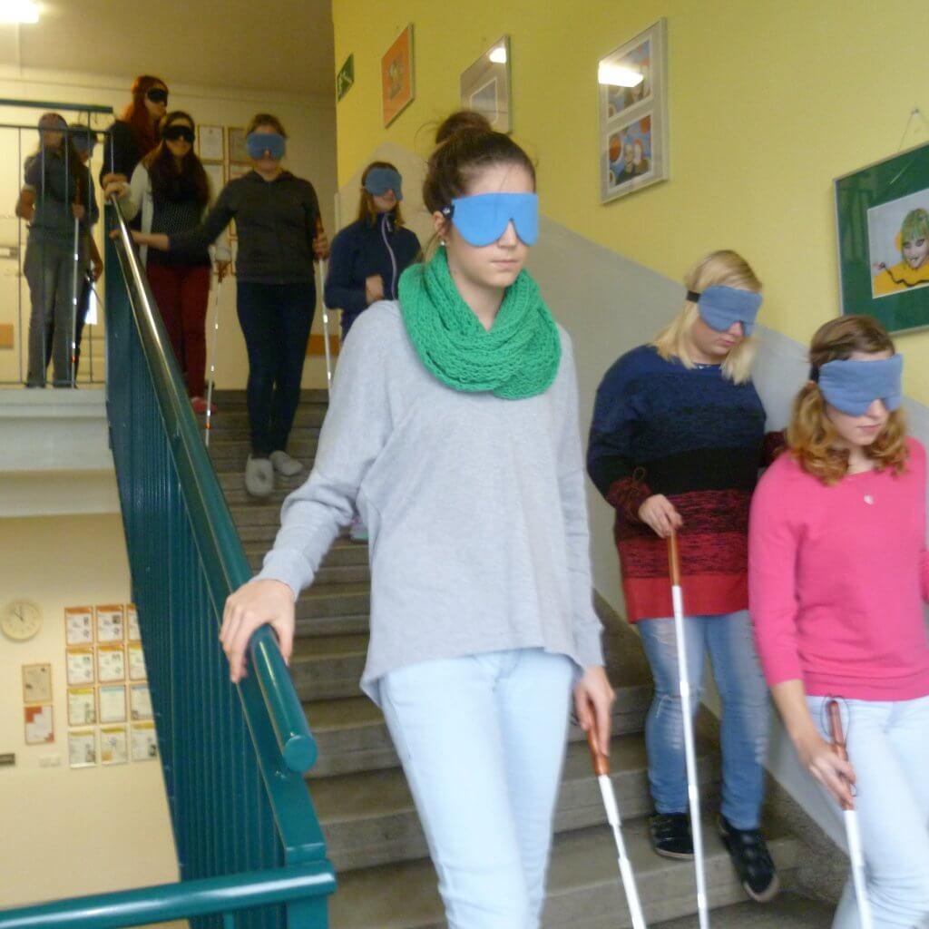Jugendliche mit Blindenstock und Dunkelbrille tasten sich die Stiegen abwärts, manche am Geländer manche an der Wand
