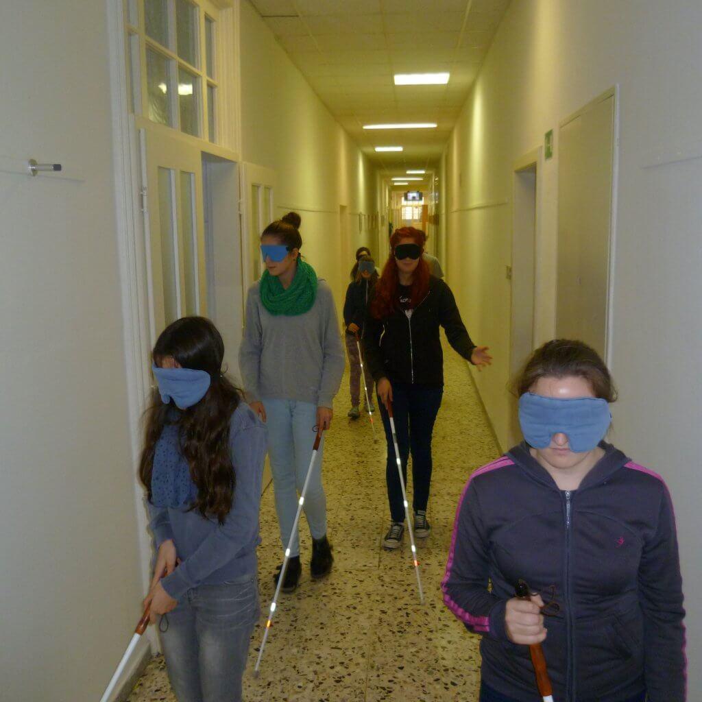 Jugendliche mit Blindenstock und Dunkelbrille tasten sich einen schmalen Gang entlang