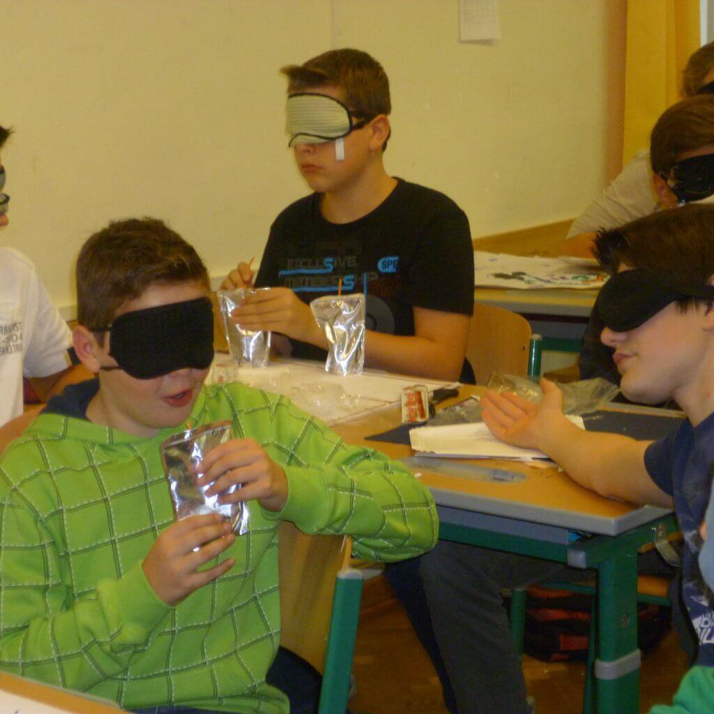 Mehrere SchülerInnen mit Dunkelbrille unterhalten sich und jausnen