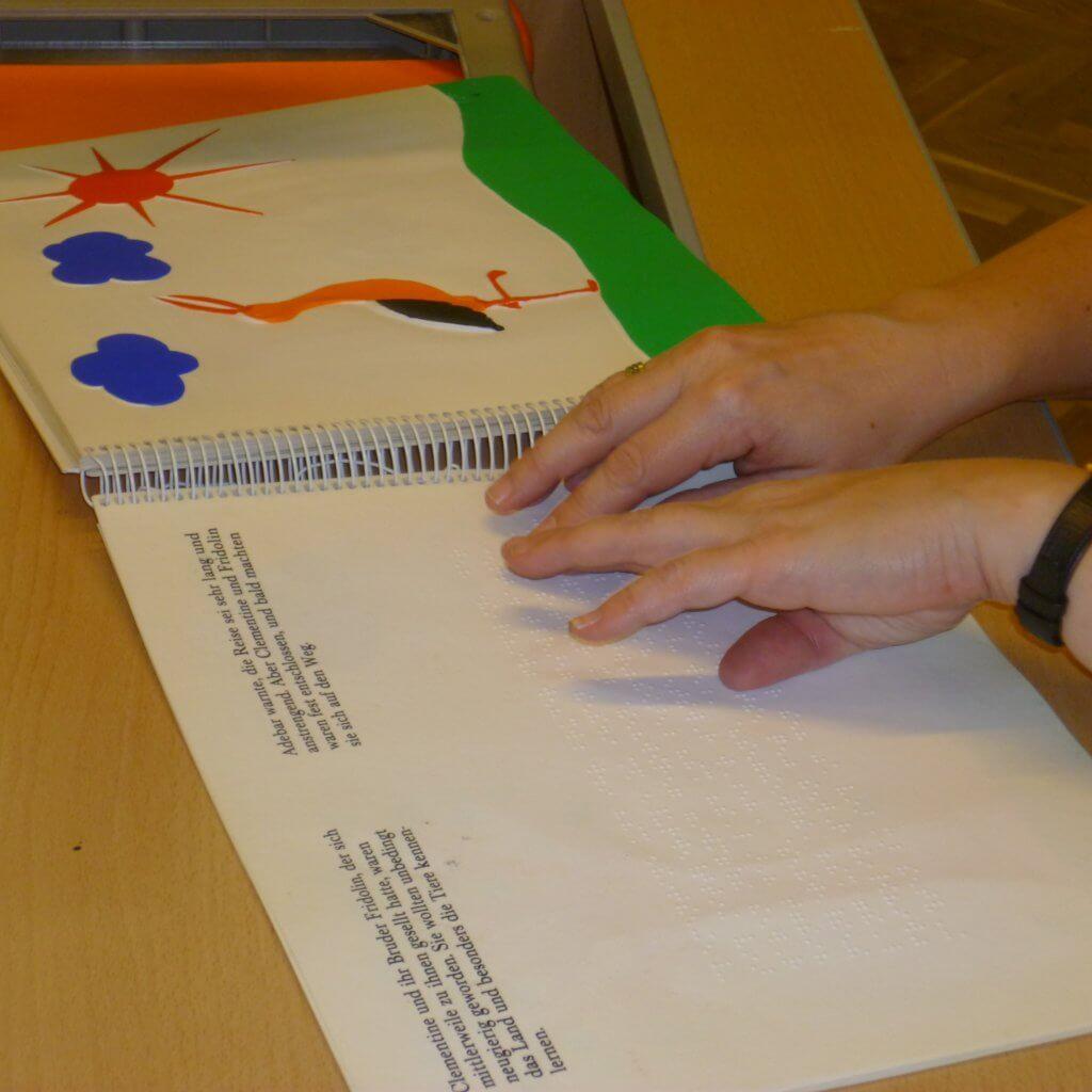 Sabine liest Braille Kinderbuch man sieht ihre Hände auf dem Buch