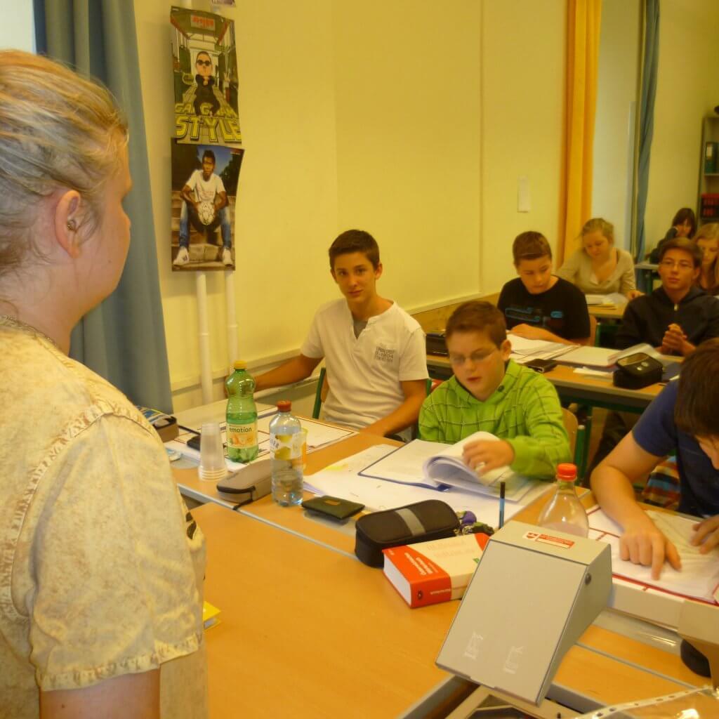Sabine steht vor Klasse die sich Braille Stadt Land Fluss anschauen