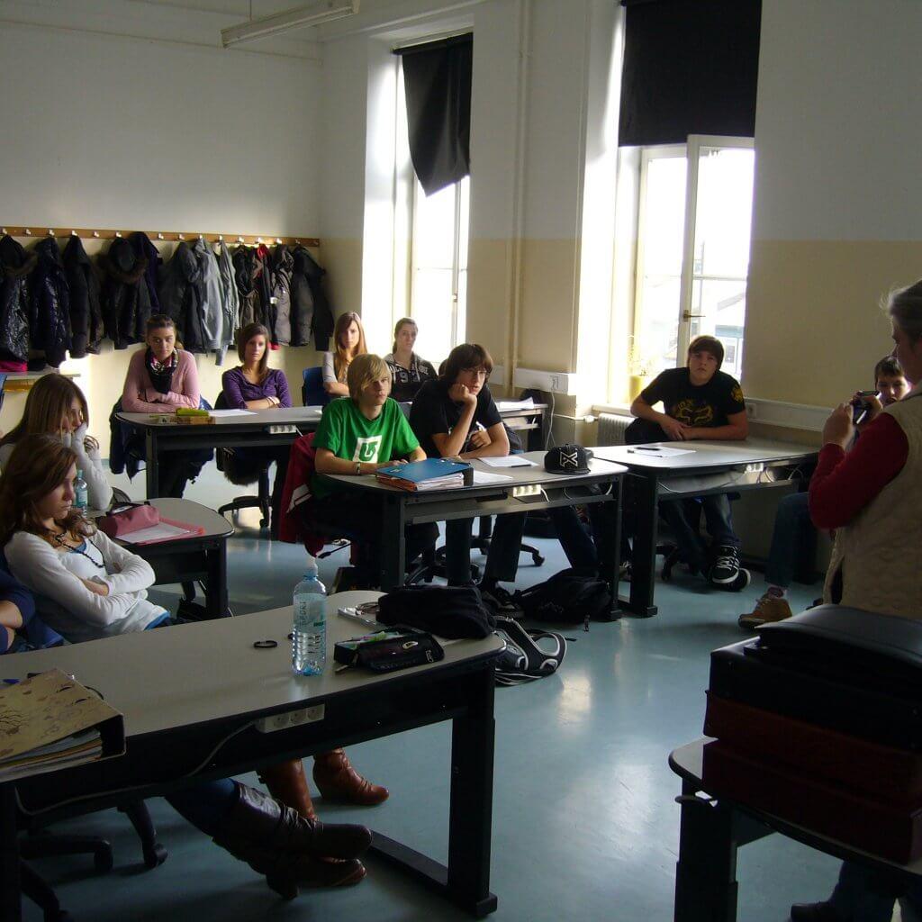 Sabine steht vor Klasse und erklärt den Colortester Klasse schaut interessiert zu