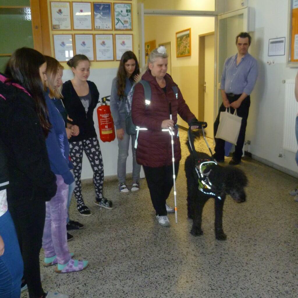 Sabine zeigt Leas Führhundkenntnisse vor, Jugendliche stehen im Halbkreis um die beiden