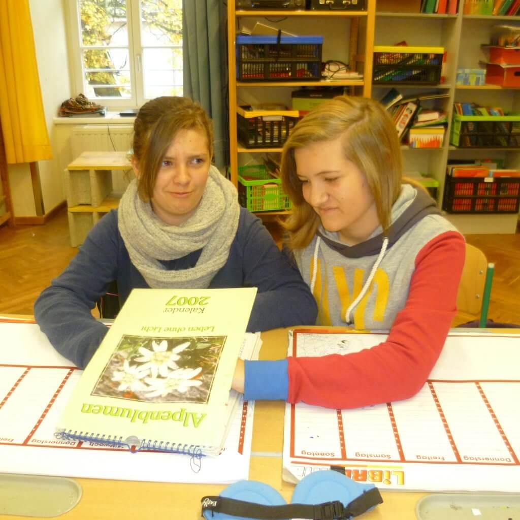 Schülerin tastet mit verwundertem Blick in zugeschlagenem Braille Kalender