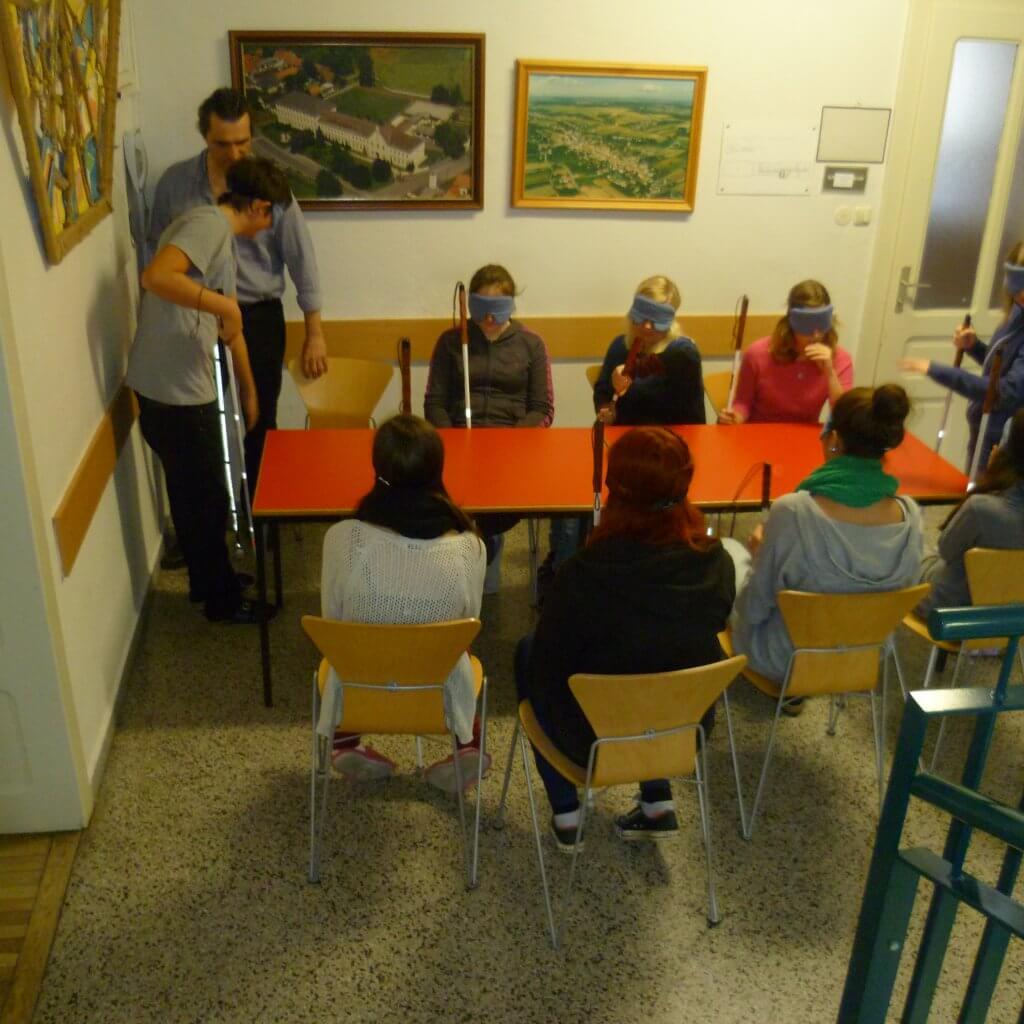 Sieben SchülerInnen sitzen an Tisch, Harald zeigt einem achten den Sitzplatz, neunte sucht selbst einen freien Platz