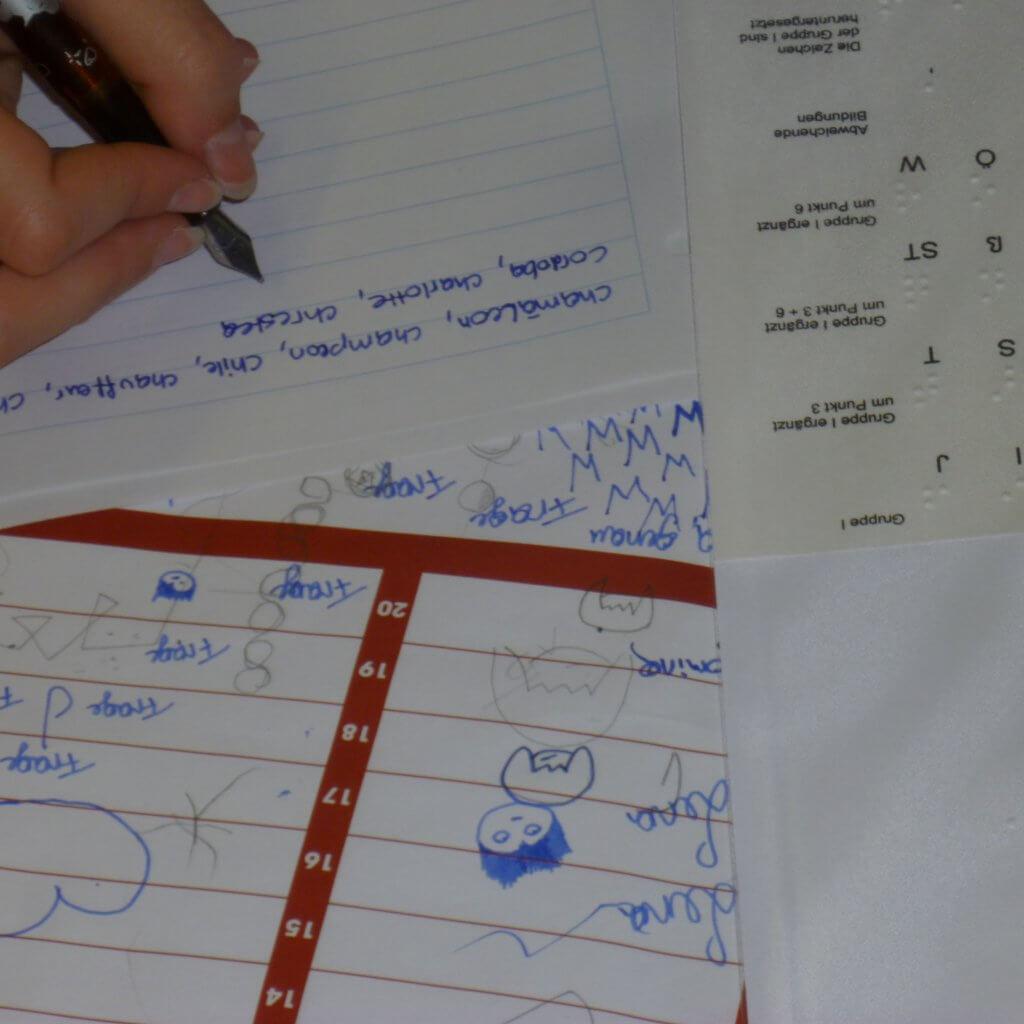 Stadt Land Fluss Braille Spiel. Hand schreibt neben Braille Alphabet gelesene Begriffe auf