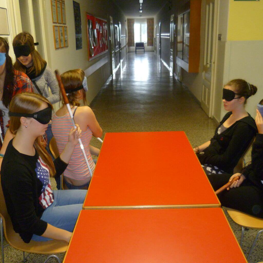 Vier Jugendliche mit Blindenstock und Dunkelbrille sitzen an Tisch, zwei tasten sich links vorbei zu freien Plätzen