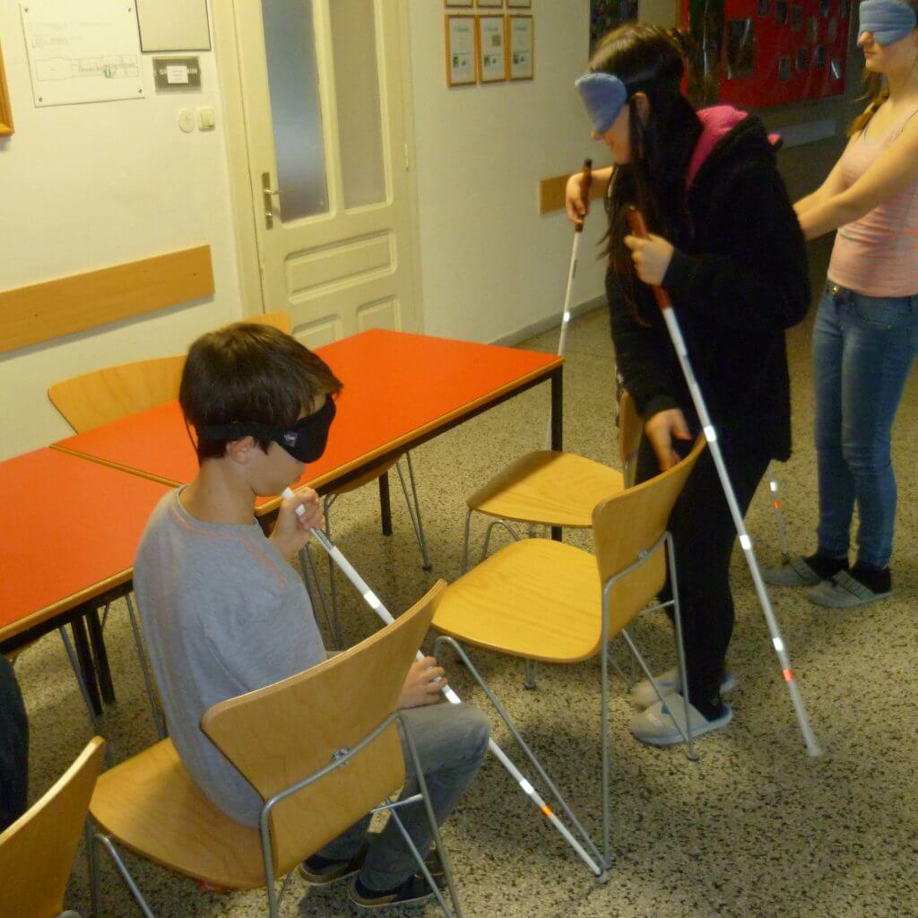 Zwei Jugendliche mit Blindenstock und Dunkelbrille sitzen an Tisch weitere drei suchen tastend einen Sitzplatz