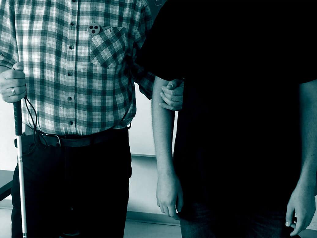 Eine Person mit Blindenstock und einem Button mit dem Blinden-Symbol am Hemd steht eingehängt mit einer anderen Person.