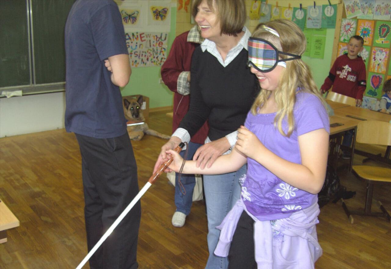 Ein Kind geht mit Blindenstock und lacht