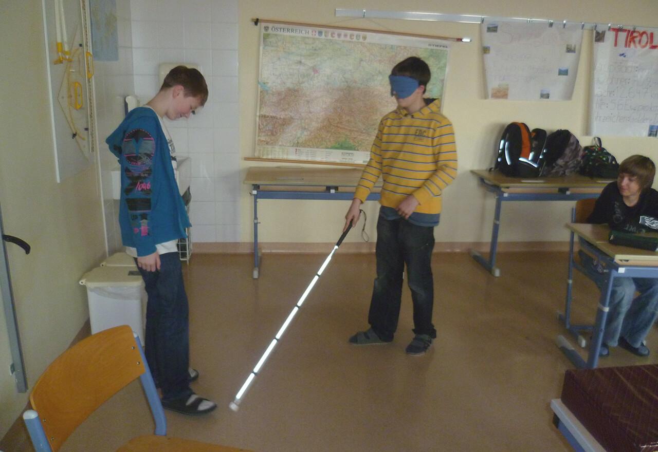 Schüler mit Blindenstock gehend vor anderem Schüler