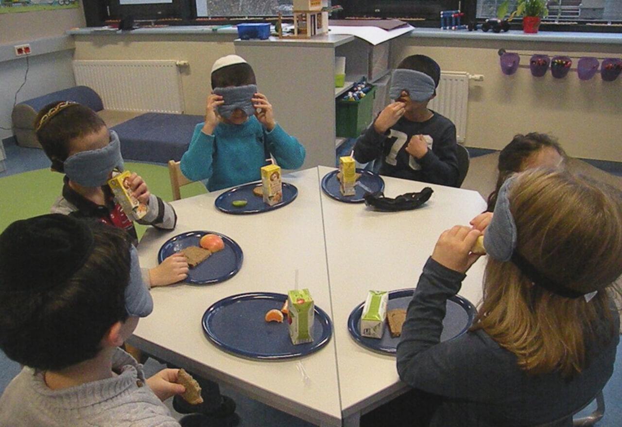 Kinder mit Dunkelbrille sitzen um einen sechseckigen Tisch und essen Jause