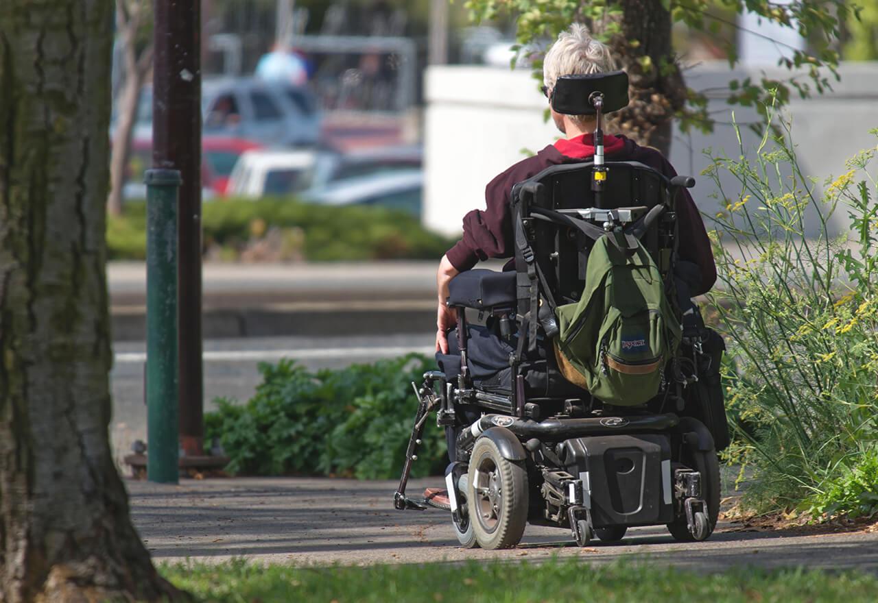 Eine Person in einem motorisierten Rollstuhl fährt einen Weg entlang. Man sieht sie von hinten.