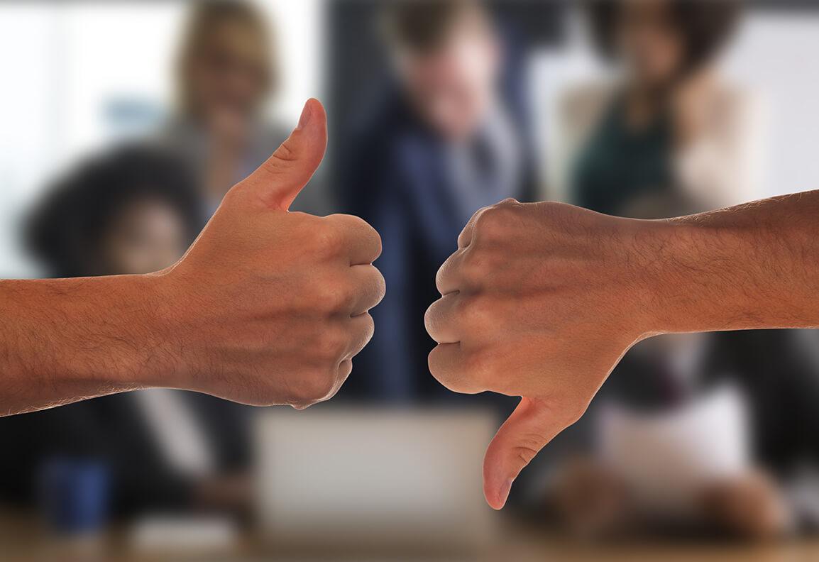 Eine Hand links im Bild mit Daumen nach oben, gegenübereine Hand mit Daumen nach unten.