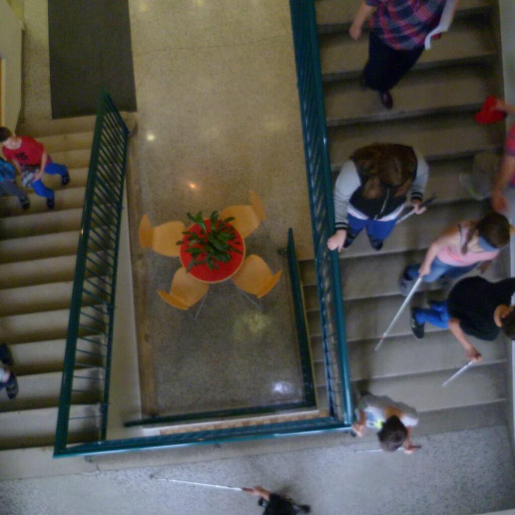 Ein Bild aus der Vogelperspektive das einen Stiegenabgang zeigt, auf dem einige Jugendliche mit Blindenstock abwärts gehen.