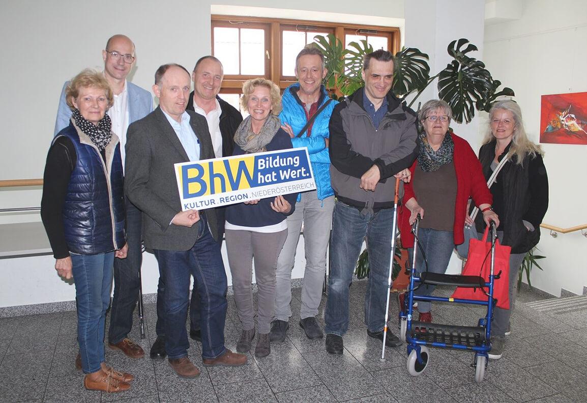 """Eine Gruppe von 9 Personen, darunter Harald von TROTZ-DEM, steht zusammen in einem Raum vor einem Fenster. Sie halten ein Schild mit dem Logo von BhW Bildung hat Wert hoch und blicken in die Kamera. Auf dem Schild steht unter dem Logo """"KULTUR.REGION.NIEDERÖSTERREICH."""""""