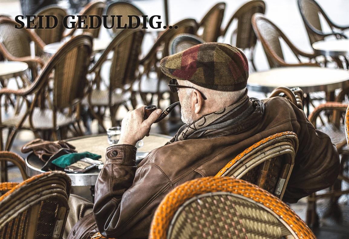 """Ein älterer Mann mit Kappe und Brille sitzt auf in einem Cafe, raucht Pfeife und ist in die Ferne gerichtet. Darüber steht """"Seid Geduldig"""""""