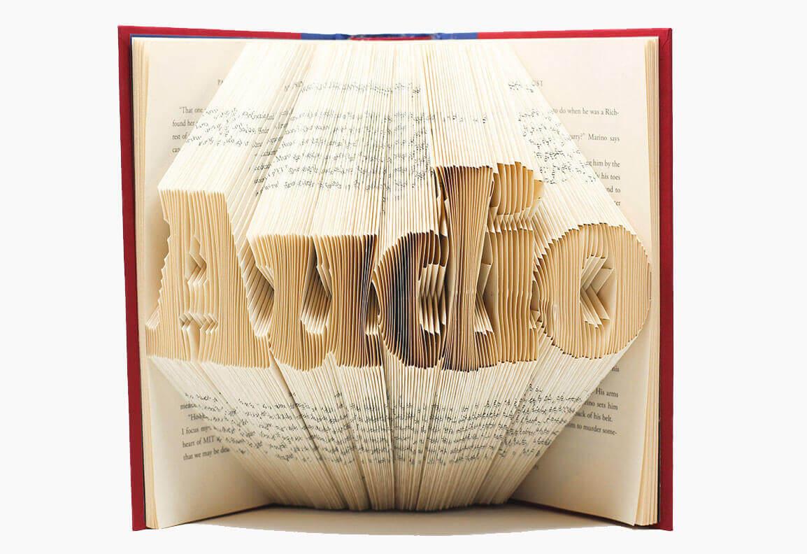 Aufgestelltes Buch, die Seiten stehen wie ein Fächer in Richtung Kamera, aus den Seiten ist das Wort Audio ausgeschnitten