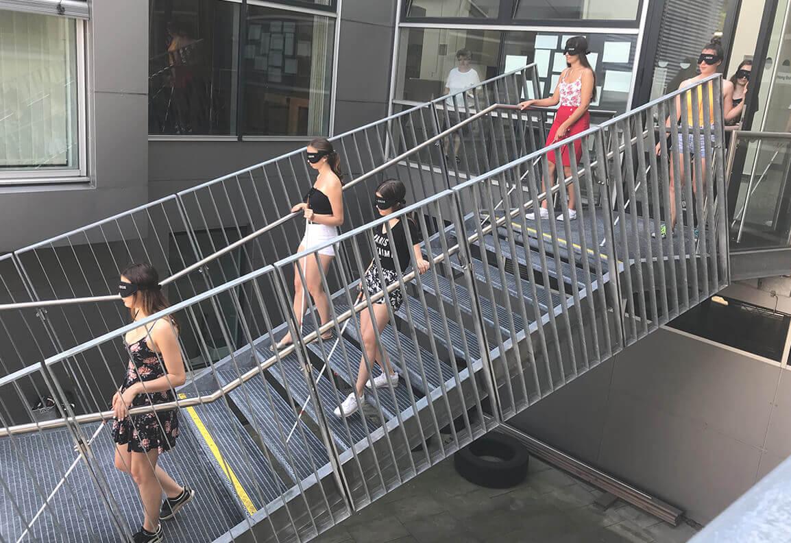 Jugendliche mit Dunkelbrille und Blindenstock gehen durch Glastür auf Treppe mit Gitterboden im Freien
