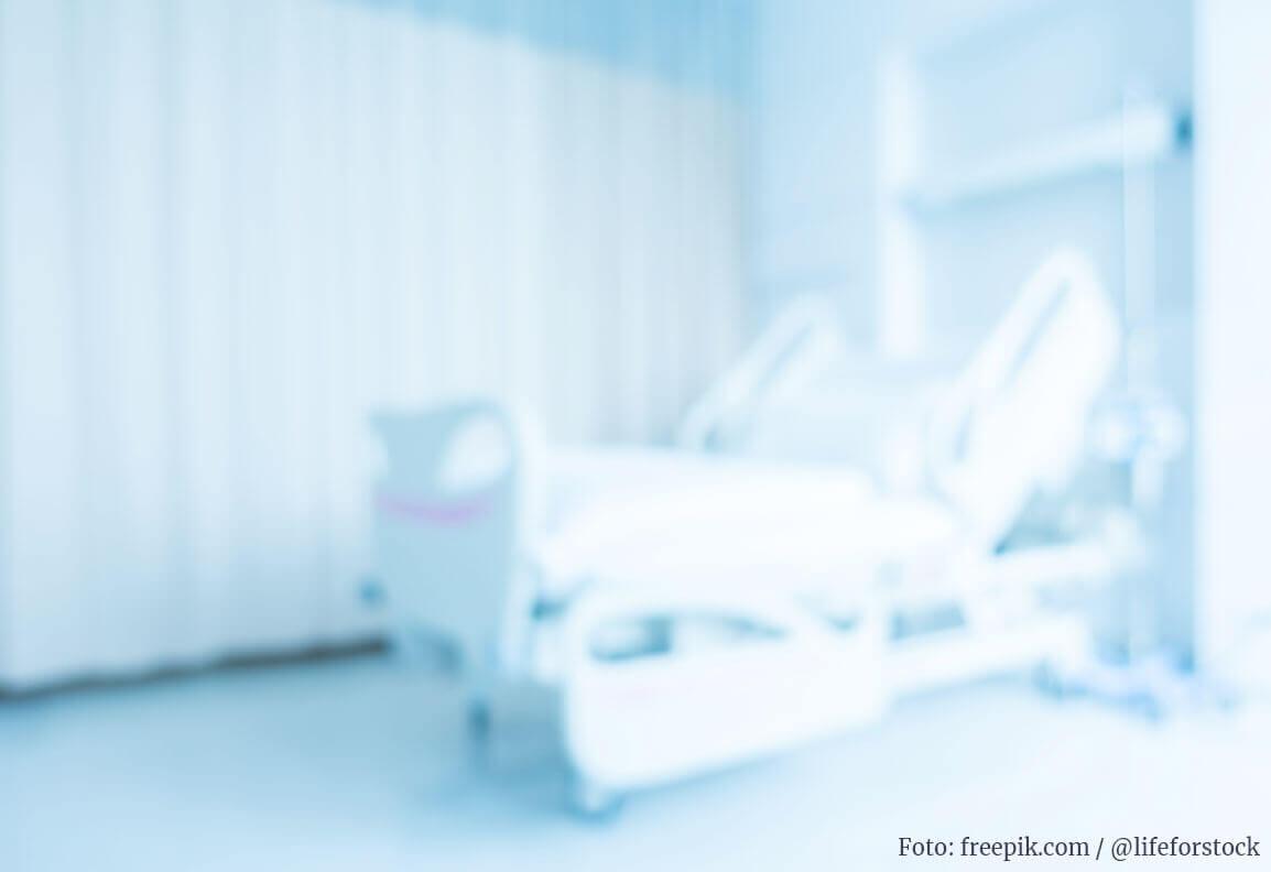 Verschwommene Sicht in ein weißes Krankenhaus-Zimmer mit Vorhang