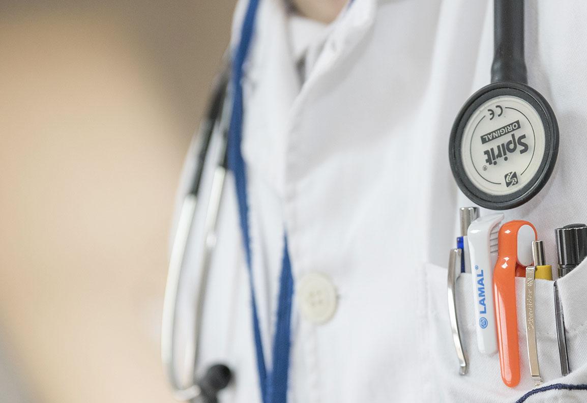 Nahaufnahme einer Person im weißen Kittel mit Stetoskop um Hals und vielen Stiften in Brusttasche