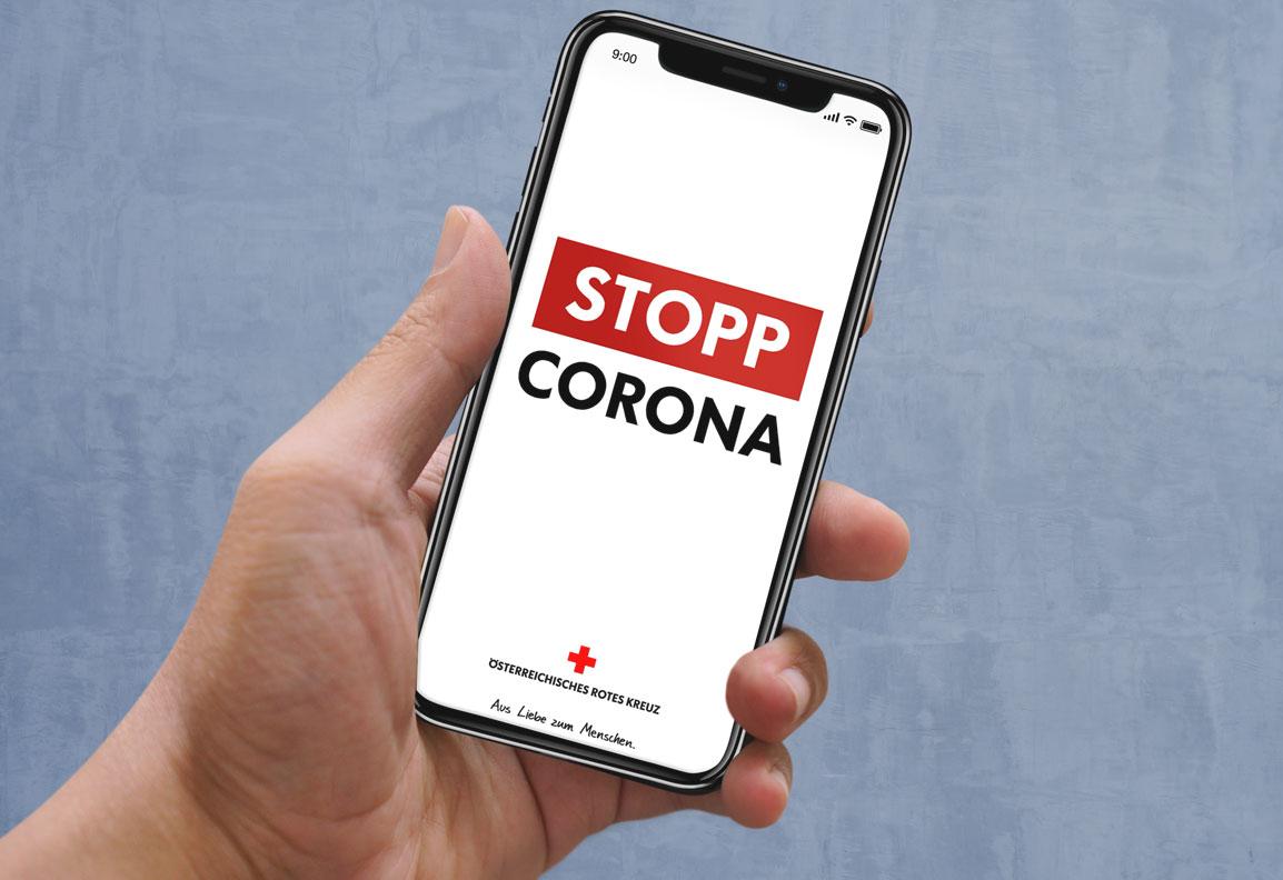 Hand hält ein Smartphone mit Startseite der Stopp-Corona App