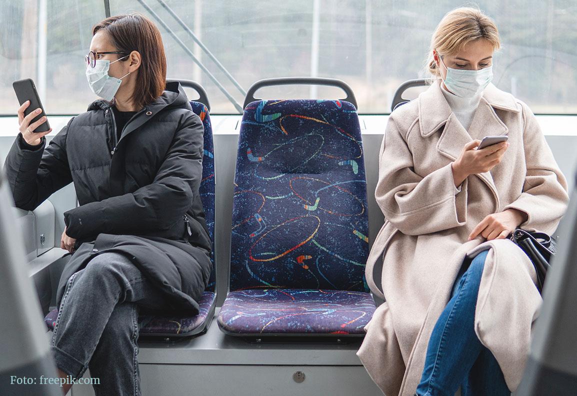 Zwei Frauen mit OP-Mundschutz und Smartphone sitzend im Bus