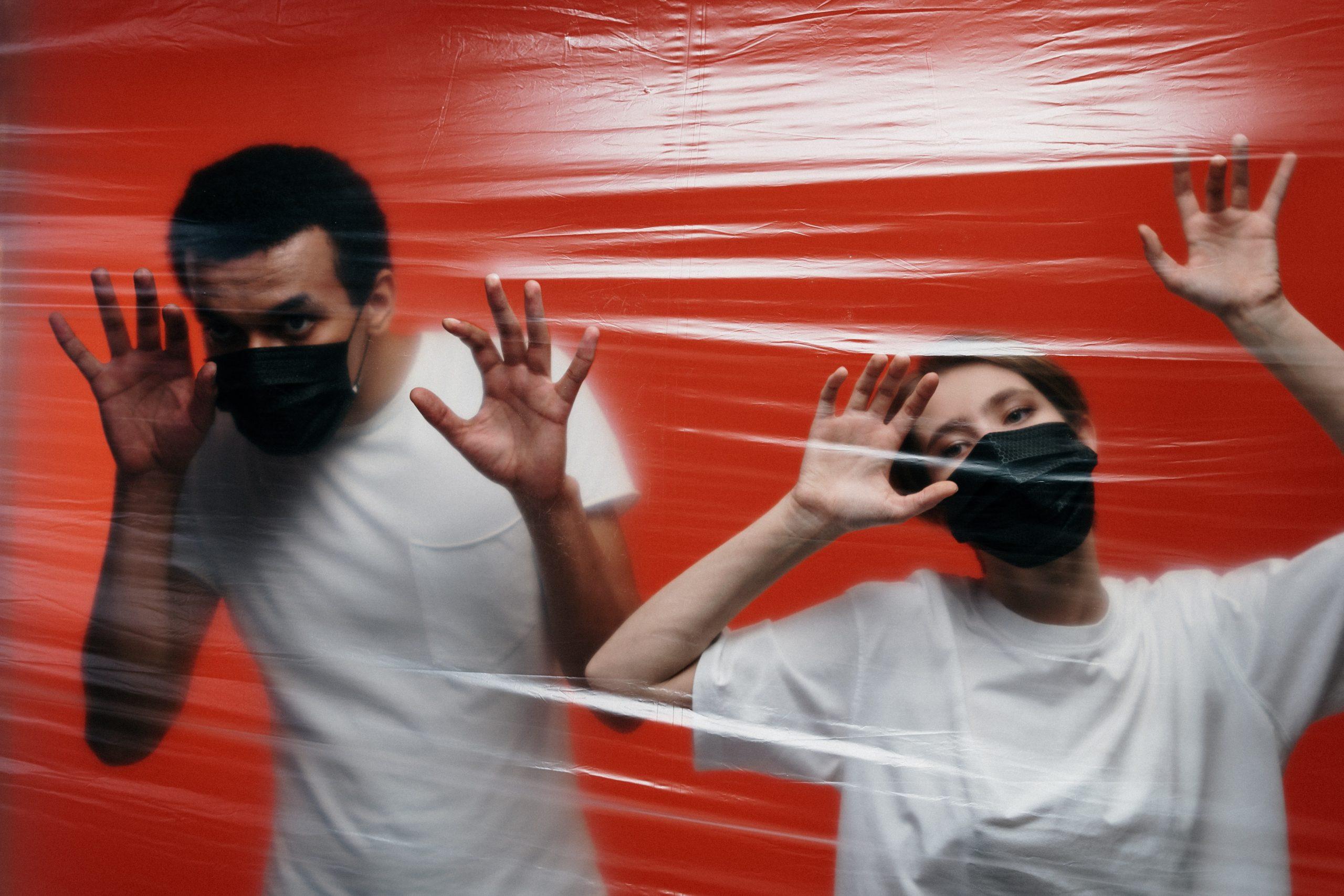 Zwei Menschen mit schwarzem Mund-Nasen-Schutz hinter einer Plastik-Folie vor einer roten Wand