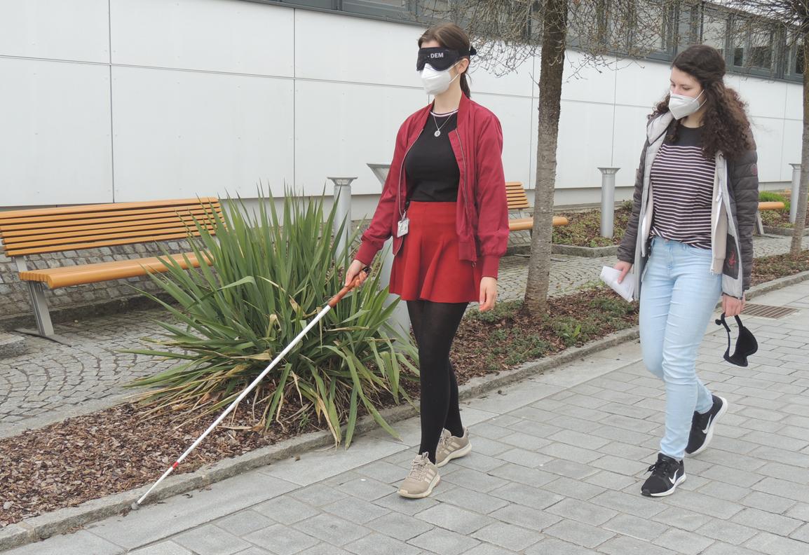 Eine Teilnehmerin mit Blindenstock und Augenbinde tastet sich einen Randstein entlang, eine weitere beobachtet sie