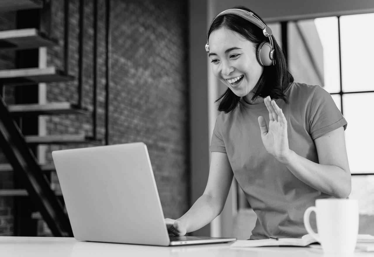 Frau mit Kopfhörern winkt in einen Laptop-Bildschirm